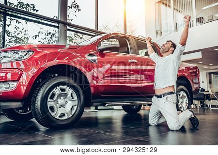 Happy Owner Of New Automobile Kneeling, Posing And Holding Hands Up. Bearded Man Standing On Knees B