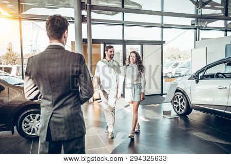 Young Family Comes Into Car Dealership To Choose The Car To Buy It. Manager Meets A Young Couple In