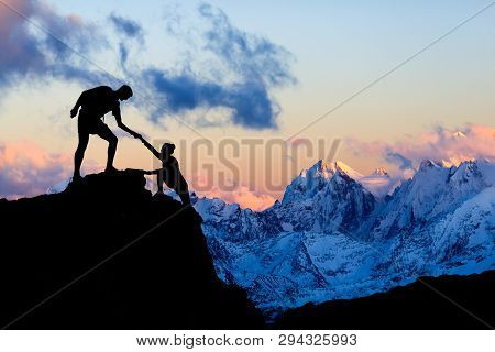 poster of Teamwork couple helping hand, trust in mountains. Team of climbers man and woman hiking, help each other on top of mountain, climbing together, inspiring sunset on Elbrus, Russia.