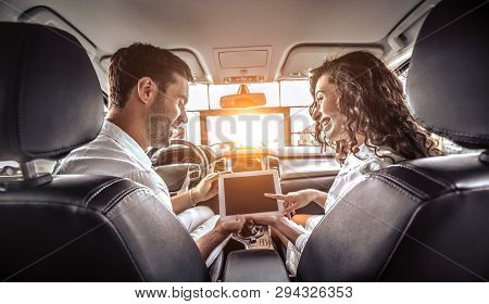 Couple Is Looking On Tablet In A New Car. The Are Looking Options Of Brandnew Car. Young Family Want