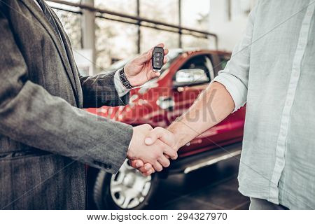 Buying A New Car. Handshake And Handing Over The Keys To The Car By The Salon Consultant To The Buye
