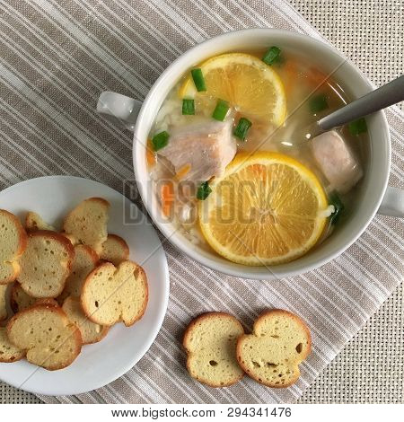 Delicious Chicken Soup With Lemon, Rise, Carrot, Green Onion And Bread Sticks Aside. Top View. Soup