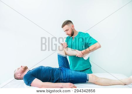 Young Male Receiving Massage From Therapist. A Chiropractor Stretching His Patient's Legs In Medical
