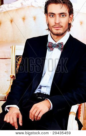 Portrait of a handsome fashionable man posing in the interior. poster