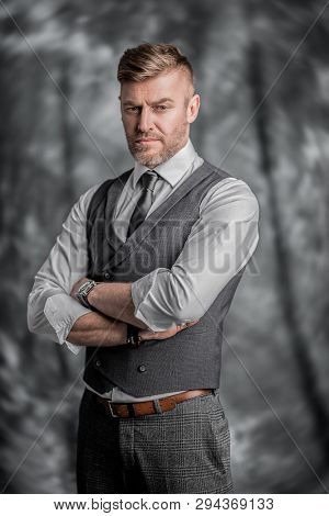 A portrait of a handsome brutal mature man posing in the studio. Casual formal fashion, men's beauty.