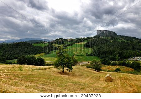 view of the famous Bismantova rock quoted in the Divine Comedy, in the mountains in northern Italy with constrasts and a dramatic sky poster