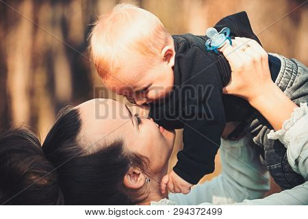Happy Family Enjoy Sunny Day. Mother Kiss Little Son With Love. Woman Play With Child. Mom And Baby