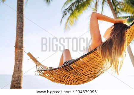 Young Beautiful Blonde Longhaired Woman Relaxing In Hammock Under Palm Trees On The Sand Beach