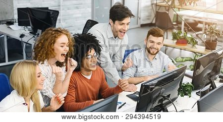 Young team of excited stock exchange traders celebrating success in office, looking at computer and shouying, panorama poster
