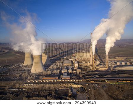 Aerial Shot Of Coal-fired Power Plant And Its Cooling Tower With Steam Rising From It
