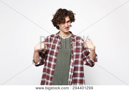 Portrait of perplexed young man in casual clothes looking camera and pointing index fingers on himself isolated on white wall background. People sincere emotions lifestyle concept. Mock up copy space. poster