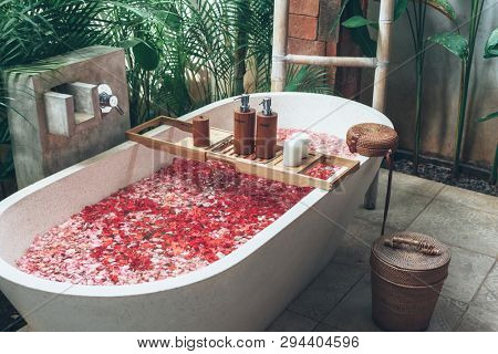 Bathtub with flower petals and beauty products on wooden tray. Organic spa relaxation in luxury Bali outdoor bath.
