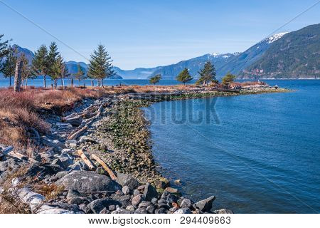 Fantastic view over ocean, snow mountain and rocks at Burrard inlet in Vancouver, Canada.
