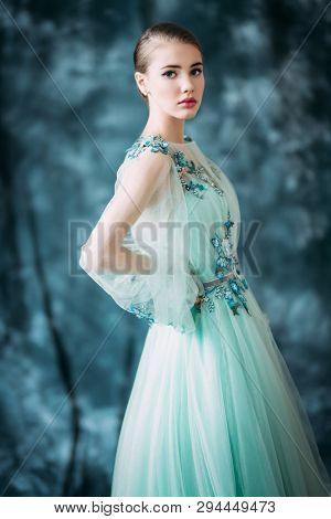 A portrait of a mysterious lady in a fluffy light green  dress with flowers posing indoor. Fairy tale, fashion.