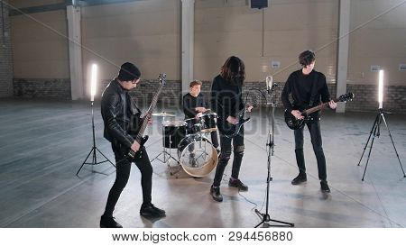 A young rock group having a repetition in a hangar. Members of a group wearing black clothes poster