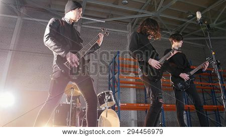 A rock group having a repetition. Guitarists in black clothes playing their parts and drummer on the background poster