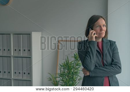 Serious Businesswoman Talking On Mobile Phone In Office And Looking Out Through The Window