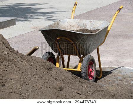 Wheelbarrow With Ground Near The Heap Of Soil. Earthworks, Urban Landscaping, Gardening Concept