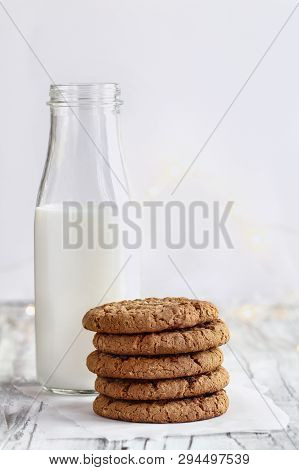 Stack Of Fresh Homemade Oatmeal Cookies With A Bottle Of Milk On A White Table Against A White Backg