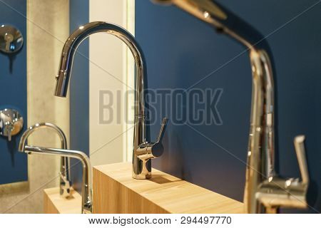 Modern Plumbing For A Stylish Luxury Bathroom. Several Metallic Shiny Steel Taps On A Wooden Blue Wa