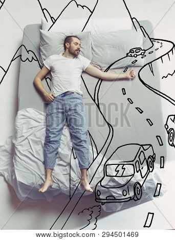Hitch-hiking On The Road. Top View Photo Of Young Man Sleeping In A Big White Bed At Home. Dreams Co