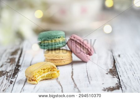 Bite Missing From A Lemon French Macaron In Front Of A Stack Of Macarons On A White Rustic Table..
