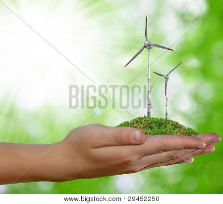 wind turbine in hand on green natural background