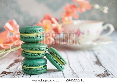 Stack Of Fresh French Green Tea Macarons On A White Rustic Table With Flowers And Antique Tea Cup Bl