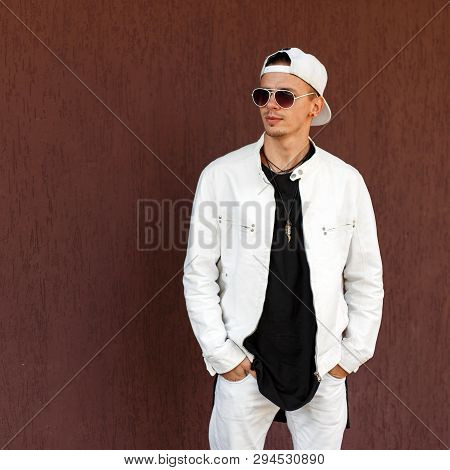 Nice Hipster Young Man In A Trendy White Summer Jacket In A Stylish Black T-shirt In A Fashionable B