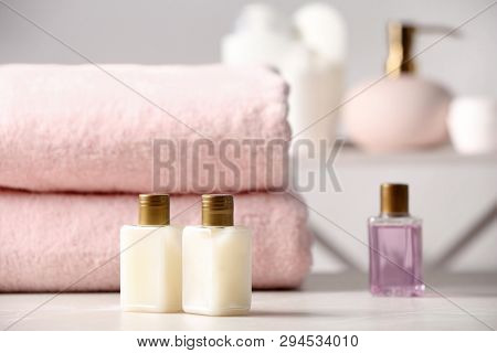 Mini Bottles With Cosmetic Products And Towels On Table In Bathroom, Space For Text. Hotel Amenities