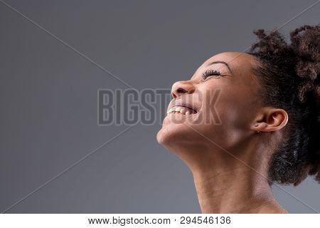 Happy Vivacious Laughing Young African Woman Tilting Her Head Back With A Joyful Smile In A Close Up