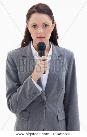 Nahaufnahme von einer schweren Businesswoman holding ein Mikrofon against white background