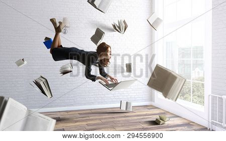 Joyful beautiful young levitating businesswoman
