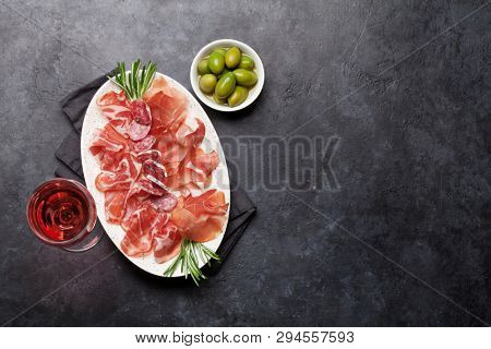 Traditional spanish jamon, prosciutto crudo, italian salami, parma ham. Antipasto plate and glass of wine. Top view flat lay. With copy space