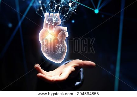 Woman s hand showing digital anatomical heart model. Mixed media.