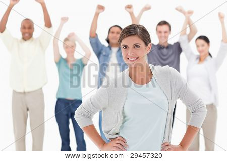 Woman smiling with her hands on her hips with people behind raising their arms against white background