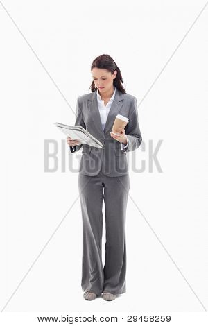 Businesswoman with a coffee reading a newspaper against white background