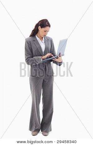 geschäftsfrau stehen und tippen auf einen Laptop against white background