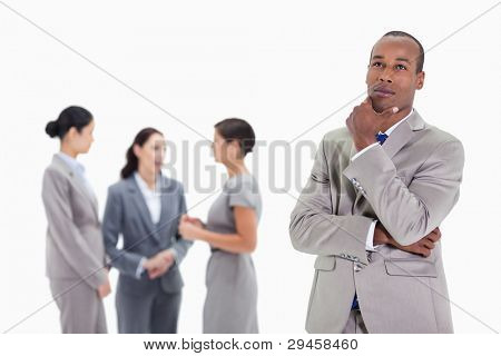 Close-up of a businessman looking up with a hand on his chin and three co-workers talking seriously in the background