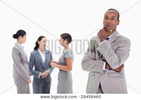 close up of a Businessman looking up mit einer Hand auf seinem Kinn und drei co-Arbeiter reden ernsthaft