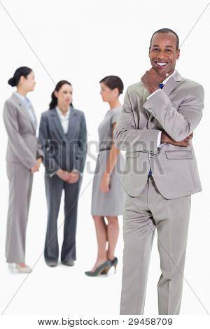 glücklich kaufmann mit einer Hand auf dem Kinn und drei co-Arbeitnehmer ernsthaft reden im Hintergrund