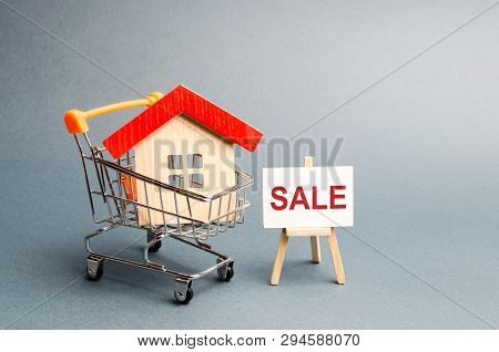 Supermarket Cart With Houses And A Sale Poster. The Concept Of Selling A Home, Real Estate Services