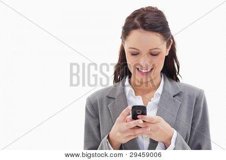 close up of a Businesswoman lächelnd und schreiben eine Textnachricht against white background