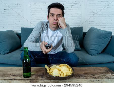 Bored Young Man Sitting On The Couch Watching Tv Switching Channels Looking For Live Sports