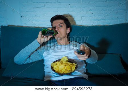 Young Man Sitting On The Couch Watching Tv Switching Channels Looking For Something To Watch At Nigh