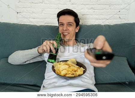 Excited And Happy Young Man Sitting On The Couch Watching Tv. Tv Programming Concept