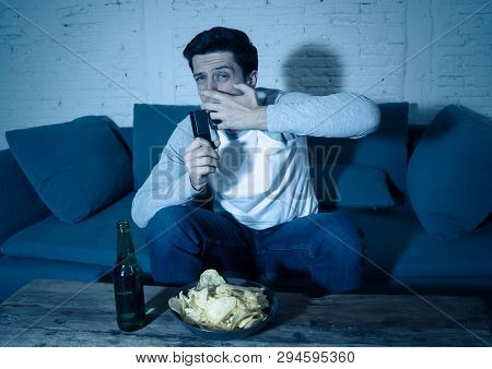 Young Man Looking Scared Sitting On Sofa Watching Tv At Night. In Human Reactions And Emotions