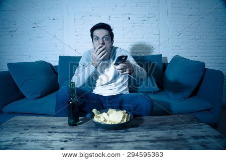Young Man Having Fun At Home Watching Horror Movie On Tv At Night.
