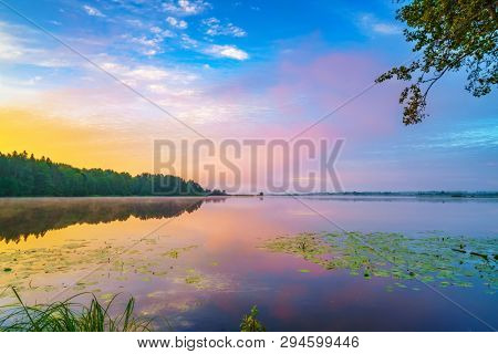 Beautiful landscape with colorful sunsrise over forest lake