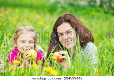 Mother and daughter lying on green meadow and eating apples
